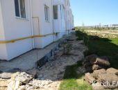Отмостку дома для переселенцев из СЗЗ Крымского моста до сих пор не отремонтировали (фото)
